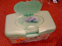 I normally use a wipes warmer for my wipes but while traveling I just use an old Huggies container and learned how to pop up the wipes just like disposable one's from this tutorial:
